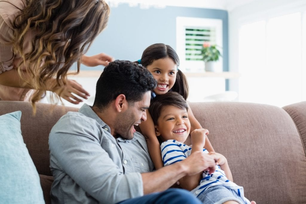 Parents and kids having fun in living room